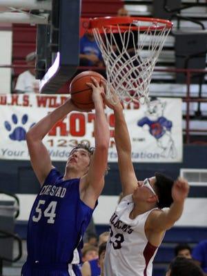 Cavemen junior center Brenden Boatwright attempts a quick shot underneath the basket Saturday at Deming.