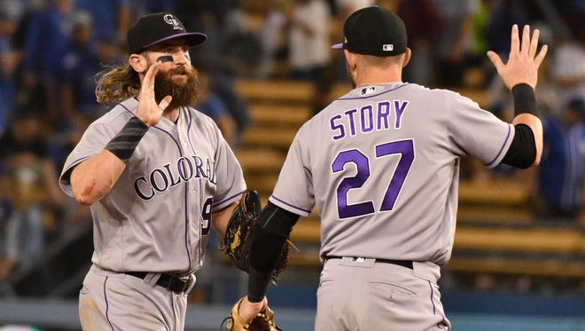 Colorado Rockies center fielder Charlie Blackmon (19) and  shortstop Trevor Story (27) celebrate the Rockies' 6-5 win over the Los Angeles Dodgers at Dodger Stadium.