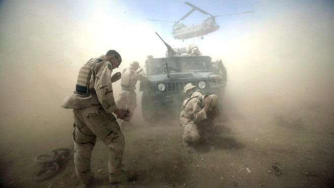 Courage: High in the mountains of Kandahar's Minashan district in Afghanistan, soldiers brave 100-m.p.h. wind from a CH47 Chinook helicopter. Their mission was to help provide stability for a 2004 presidential vote.
