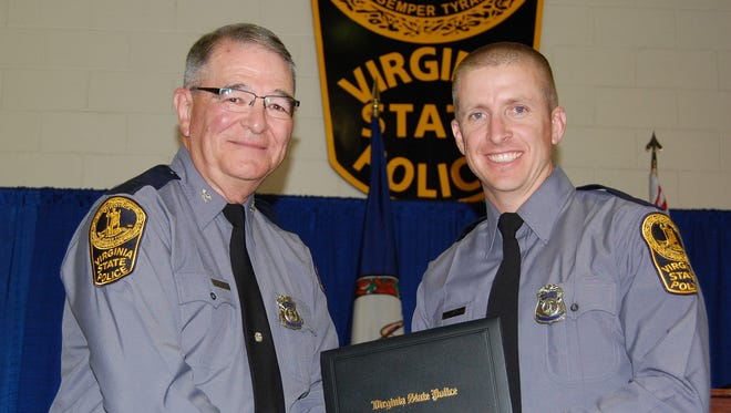 In this November 2014 photo provided by the Virginia State Police, trooper Chad P. Dermyer, right, poses for a photo as he receives his graduation diploma from Superintendent Col. W. Steven Flaherty. Flaherty said Dermyer died Thursday, March 31, 2016,  after being shot multiple times at a Greyhound bus station in Richmond, Va. The gunman was shot dead by two other troopers.
