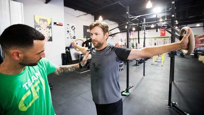 Professional golfer, George McNeill works out at Iron DNA Fitness under the guidance of owner/trainer, Seth Hayes on Thursday morning. McNeill is recovering from a shoulder injury. He will compete at the Yuengling Open at the Fort Myers Country Club this weekend. He is also competing in more events throughout the year.