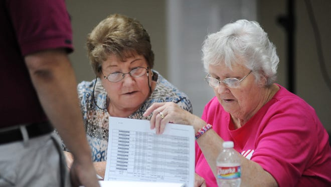 Poll workers Ann Robertson, left, and Pat Chism try to find a man's name on the voter rolls at the precinct located at the Victory Community Church building in Madison during the June 3 Republican Party primary.
