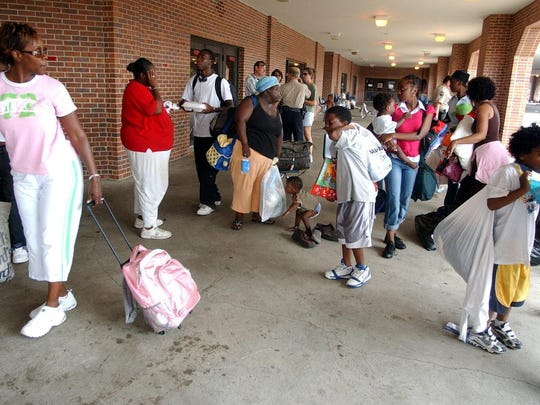 Lena Turner, left, of Lafayette leads a family of evacuees from New Orleans away from the Cajundome on Saturday. Turner was taking the family to her home to shelter them.