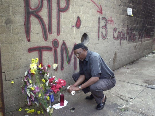 April 8, 2001: Jerome Manigan lights a candle at a