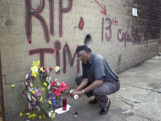 April 8, 2001: Jerome Manigan lights a candle at a makeshift memorial to Timothy Thomas near the sight where he was killed.
