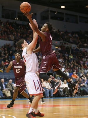 Aquinas's Earnest Edwards drives to the basket against Fairport's Matt Muncey (21). Edwards scored 23 in a 47-43 Aquinas win in the Class AA final.