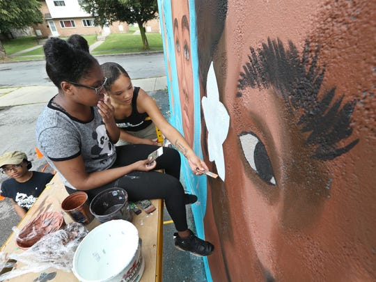Kaori-Mei Stephens, right, lends a helping hand to Etana Browne, center, as they paint highlights around a flower as Nzinga Muhammad, left, goes to get more paint as the trio of Rochester teen girls paint a large mural on the side of the Flying Squirrel at 285 Clarissa St. as part of Wall\Therapy 2017.