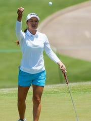 Minjee Lee tosses a ball to her caddie during round