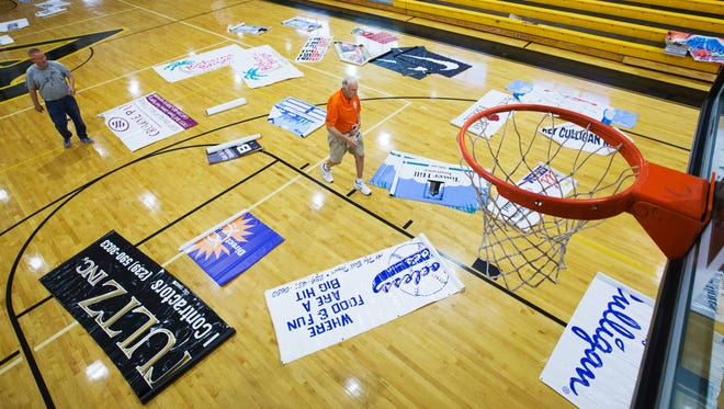 "Bill Pollock, president of Classic Basketball, Inc., center, rolls out banners Saturday at Bishop Verot High School in Fort Myers. ""I've been hanging banners for 31 years,"" Pollock said. Pollock and a group of volunteers prepared the school's gym for the upcoming Culligan City of Palms Classic."