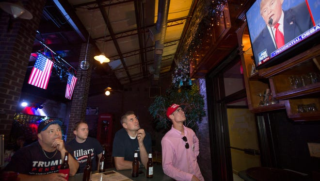 In this file photo from October 2016, supporters of Donald Trump watch a presidential debate at TK's Pub. The pub owner, Todd King, recently removed a Browns helmet from his bar because he disagrees with the NFL players who kneel for the National Anthem.