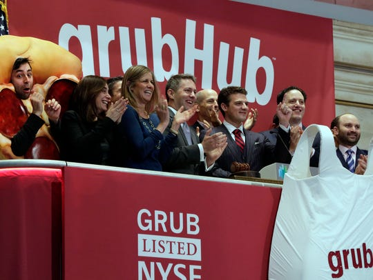 FILE - In this Friday, April 4, 2014, file photo, GrubHub CEO Matthew Maloney, third from right, is applauded as he rings the New York Stock Exchange opening bell. (AP Photo/Richard Drew, File)