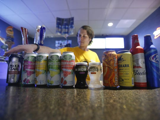 Jeffrey Maloney arranges some of the alcoholic drinks - including wines, beers, hard root beer and cider - available at Westtown Movies in Middletown. The theater also has a selection of beers on tap.