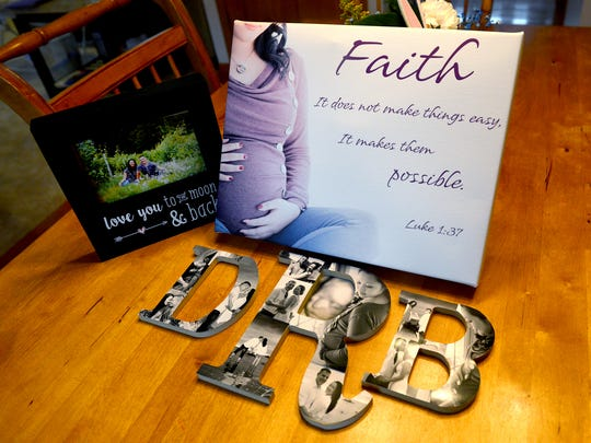 "Items created for Kate Rodeman after her husband's death sit on her kitchen table on Monday, March 28, 2016. Rodeman's husband, Dennis, was killed last fall after he was struck by a vehicle while collecting donations for the ""Fill the Boot"" campaign. She gave birth a week ago to their son Dennis Blake Rodeman."