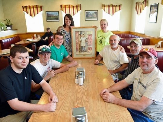The Hronis' gather at Greenvillage Restuarant on Thursday June 9, 2016. From left, clockwise are Angelo, Yianni,  Johnny, Vicki, Stella, Chris, Fotios and Bill Hronis. The ladies are holding a picture of Greenvillage Restaurant founder Angelo Hronis.