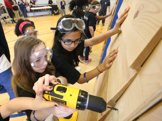 Fifth-gader Spencer Cox drills in a screw to secure the side of the house as Sophia Boyd helps hold up the siding during a Hammer Build at Hobgood Elementary Thursday, Feb. 23, 2017.