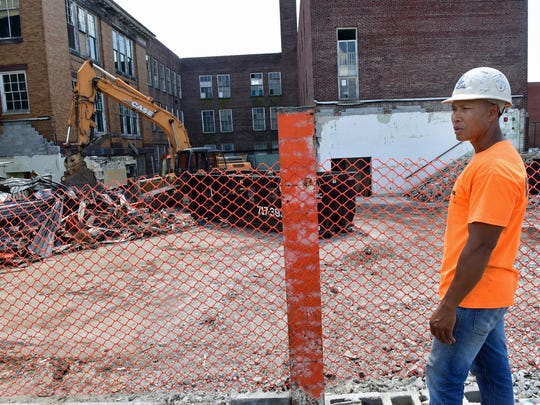 Lou Choub, of Neal Enterprises, walks past a section of  the former Central Junior High School that's being demolished on Monday, July 17, 2017. Developer Vern McKissick has plans to transform the building at Queen and Third streets into luxury apartments.