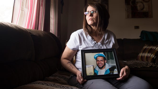 Tracy Lawrence-Felton holds a portrait of her late son, Aaron Lawrence, in her Hanover Borough home. Aaron was 20 years old when he died from a heroin overdose in July 2010. Now, nearly seven years after his death, Justin Wentz, 28, and Jennifer Busbey, 25, have been charged with providing Lawrence with the heroin and standing by as he overdosed and died.