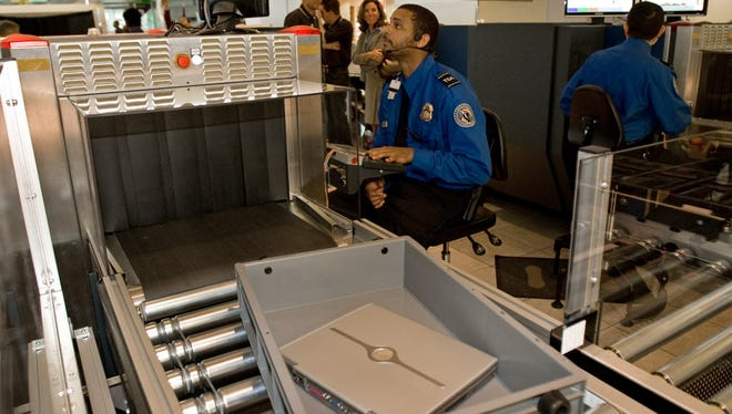 A Transportation Security Administration officer reads the X-ray of a laptop computer that rides in a new style bin for carry-ons at Baltimore-Washington International Airport's security screening checkpoint B in the Southwest terminal on April 28, 2008.