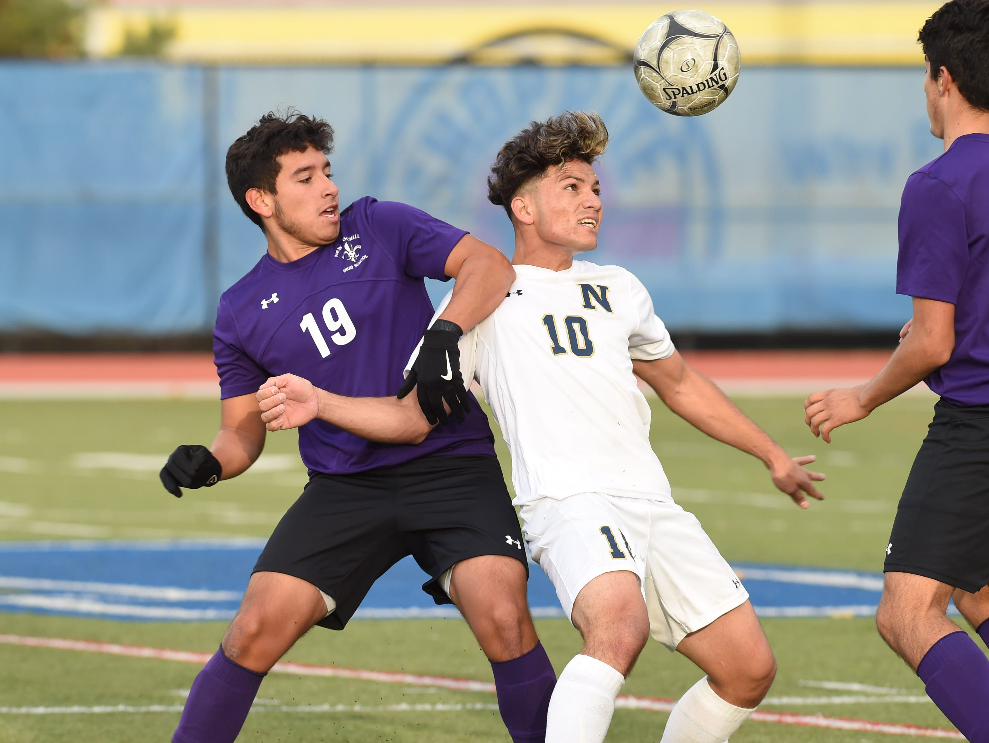 New Rochelle's Cristian Torres, left, and Newburgh's Jose Alvarez, right, fight for the ball during Saturday's Class AA regional final.