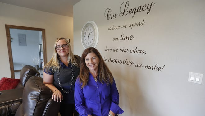 Legacy Estates founder and CEO Tina Moser, seated, and residence director Sarah Kramer pose near a wall carrying an inspirational message at the new home in Hobart for residents with dementia.