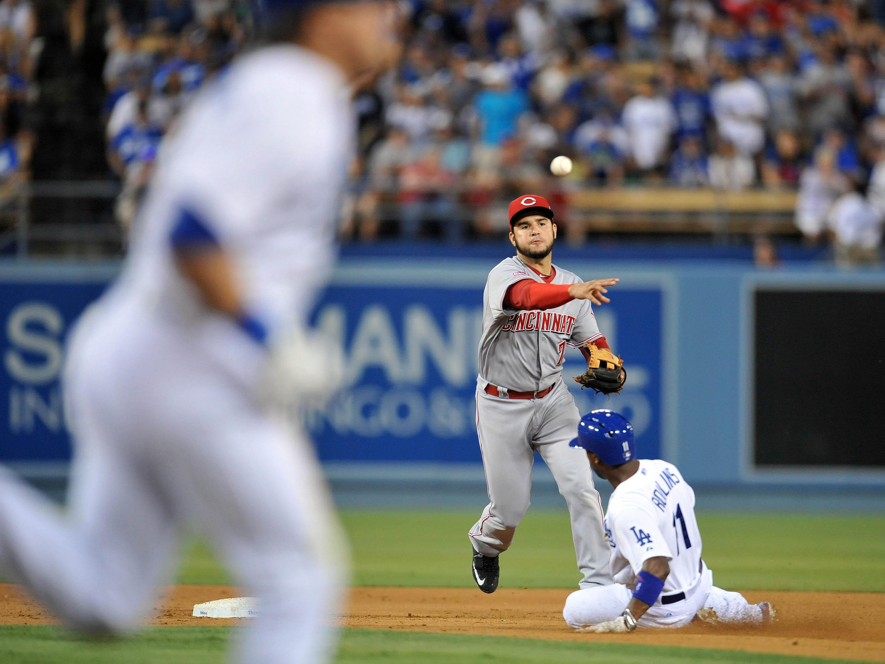 Cincinnati shortstop Eugenio Suarez throws to first base to turn a double play in the sixth inning against Los Angeles on Saturday night at Dodger Stadium.