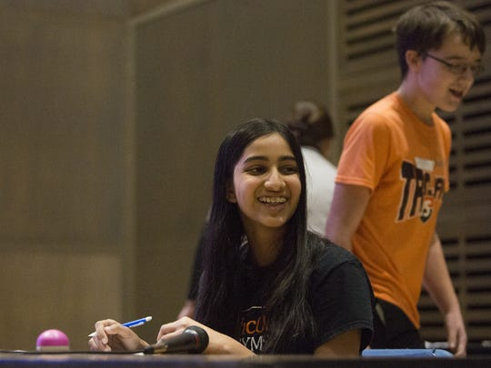 Central York Middle School's Prital Prabhu, left, smiles after eliminating York Suburban Middle School's Devlin Ravegum, right, during the final round of the annual Mathcounts competition. Students from around York County tested their math knowledge at the event, held Tuesday at York College.