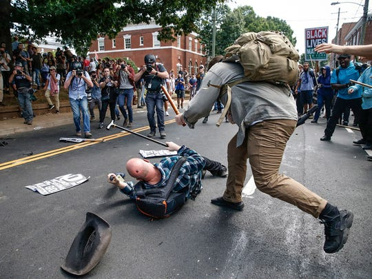 "A counterprotester clubs a man's head during a feud in the street in front of Emancipation Park, formerly known as Lee Park, during the ""Unite the Right"" rally in Charlottesville, Va., on Aug. 12, 2017."