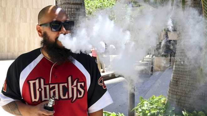 Trevor Husseini exhales a vape cloud. Hawaii is considering outlawing flavored e-cig liquids, flavored tobacco.