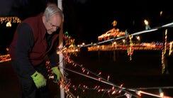 Bill Minneci looks for a plug to turn on a light figure.