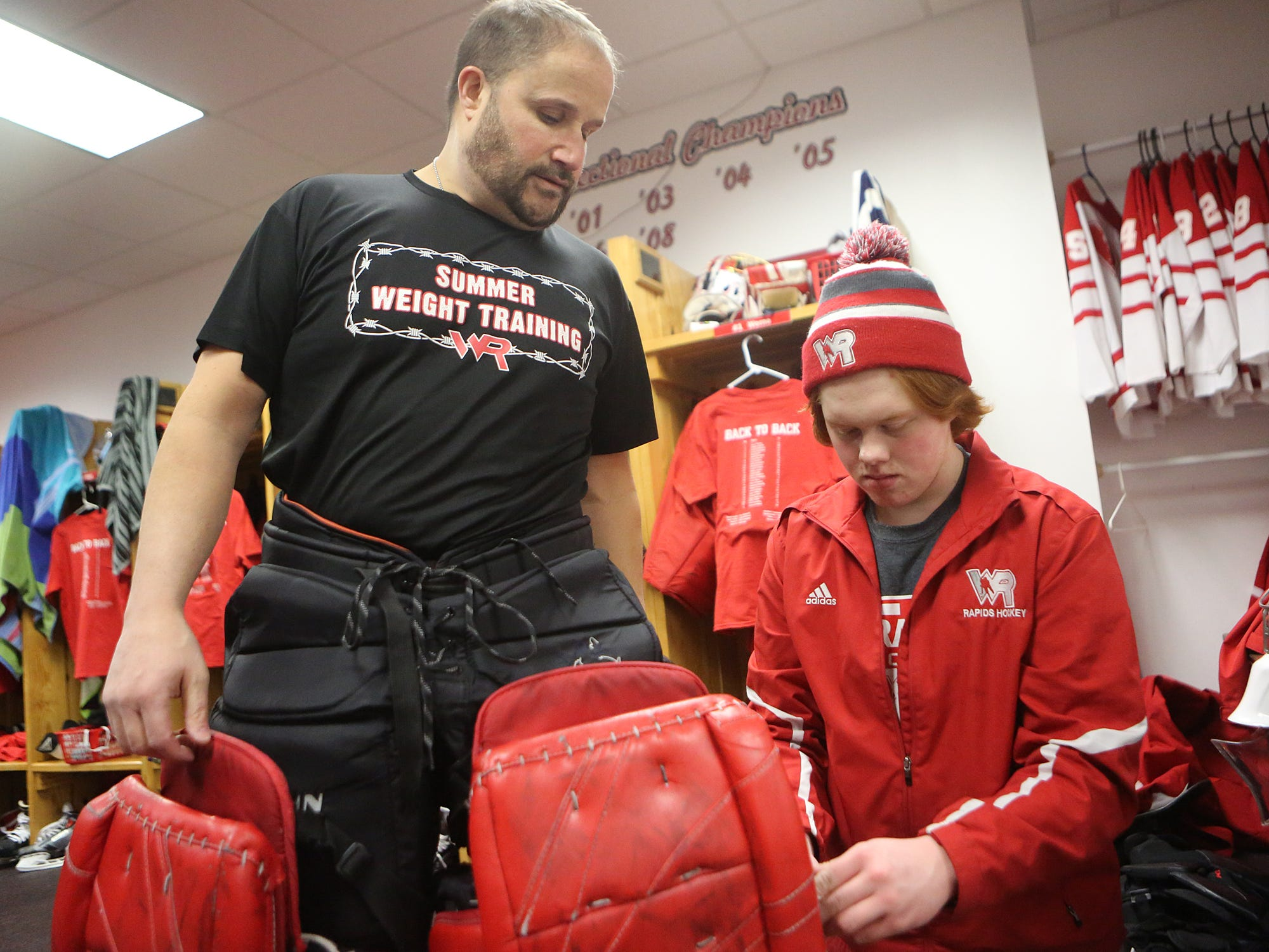 Wisconsin Rapids goalie Barry Werne, right, helps Daily Tribune Media sports reporter Mark Massoglia into goalie gear Friday at the South Wood County Recreation Center in Wisconsin Rapids.