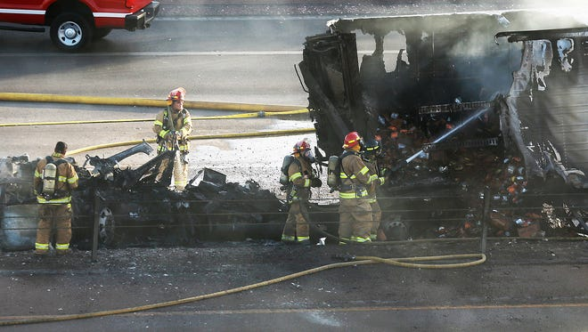 El Paso firefighters work to extinguish a fire in the trailer of an 18-wheeler involved in a multi-vehicle accident on I-10 East at Sunland Park Drive late Monday afternoon.