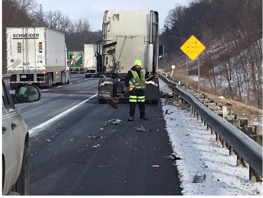 A tow truck driver helps clean debris from a crash