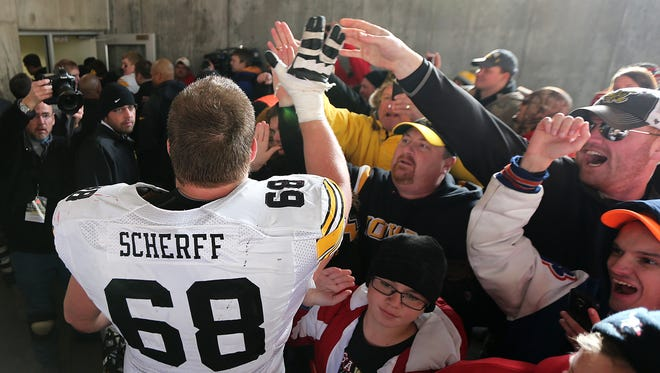 Iowa offensive lineman Brandon Scherff celebrates a win over Nebraska with fans on Friday at Memorial Stadium in Lincoln, Neb.