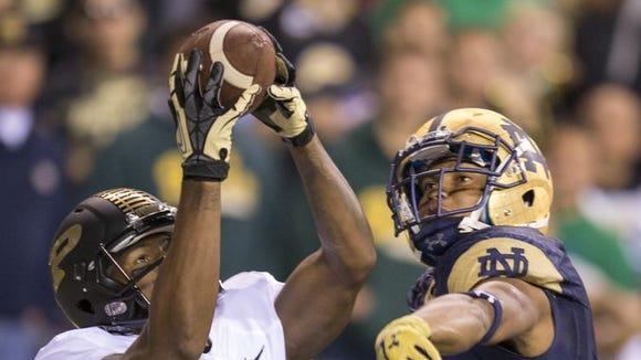 DeAngelo Yancey of Purdue, grabs a second quarter touchdown against defense by Cody Riggs of Notre Dame, Purdue and Notre Dame football at Lucas Oil Stadium, Indianapolis, Saturday, September 14, 2014.