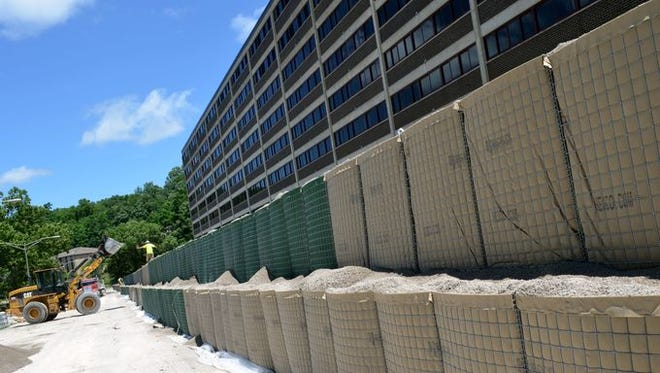 Crews assemble HESCO flood barriers Tuesday outside of the University of Iowa's Mayflower Hall along North Dubuque Street.
