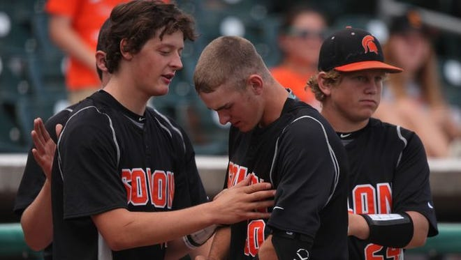 Solon's Dillon Drake, center, is comforted by teammates after a late-game rally came up short during an Iowa High School state baseball quarterfinal against Waverly-Shell Rock on Tuesday, July 29, 2014, at Principal Park in downtown Des Moines, Iowa.