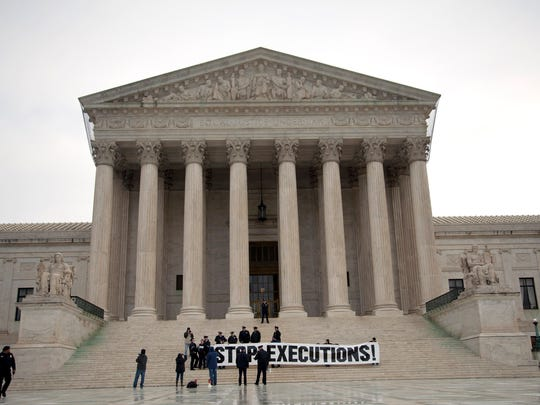 Demonstrators hold a banner on the steps of the Supreme