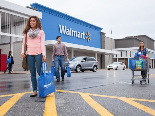 Multiple shoppers near the entrance of a Walmart store.