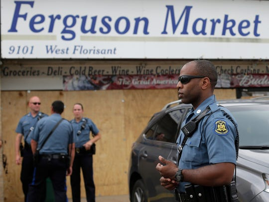 Missouri Highway Patrol troops stand watch outside a market on Friday, where Michael Brown is alleged to have stolen cigars before being killed by police nearly a week ago in Ferguson, Mo. A suburban St. Louis police chief on Friday identified the officer whose fatal shooting ignited days of heated protests, and released documents alleging the teen was killed after a robbery in which he was suspected of the theft.