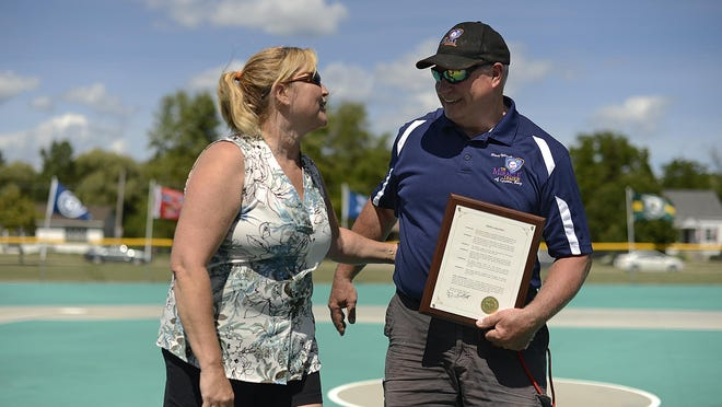 Paul Liegeois, founder and executive director of the Miracle League of Green Bay, is congratulated by Shelly Curran after Liegeois was honored Saturday at Resch Miracle Field in Allouez.