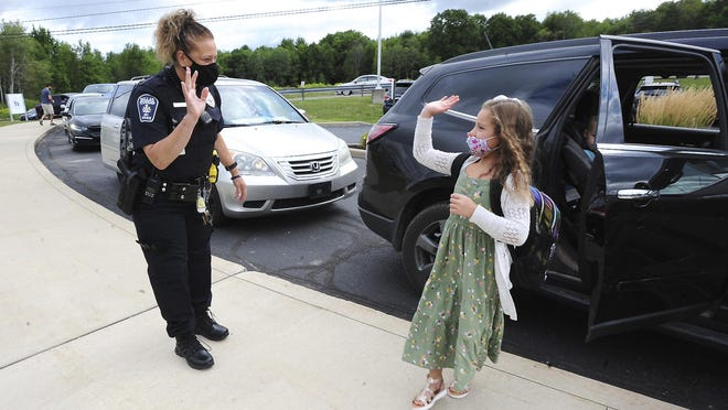 Dallas School District Intermediate second grade student Nelia Costello waves to Dallas Township Police Officer and school district resource officer Gina Kotowski on the first day of school in the Dallas School District, Dallas Township Pa., Wednesday August 19, 2020.