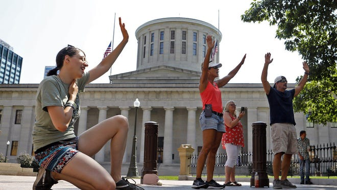 """Cristina Hodge, 28, left, joins Michelle and Bill Bolin and Connie Tucker as they worship outside the Statehouse Monday during the """"30 Days of Praise"""" gathering. Faith leaders are praying for peace and harmony there throughout the month."""