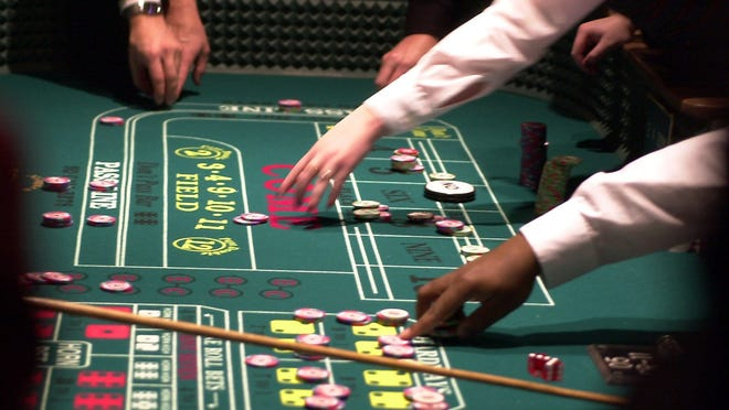 Seneca Niagara table operators reach for the chips that lost in the previous craps throw in the gaming casino in Niagara Falls. The state Gaming Facility Location Board said it's nearing a decision to issue up to four casino licenses in New York from among 16 applications.