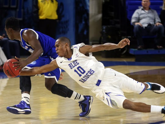 MTSU's Jaqawn Raymond dives for the ball against TSU's Xavier Richards in the second half Sunday, Dec. 21, 2014 at MTSU.