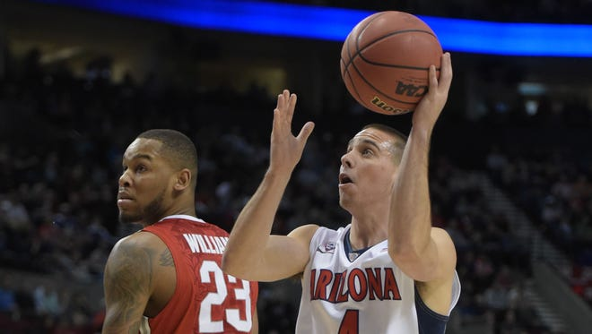 March 21, 2015; Portland, Ore.; Arizona Wildcats guard T.J. McConnell (4) shoots around Ohio State Buckeyes center Amir Williams during the first half in the third round of the 2015 NCAA Tournament at Moda Center.