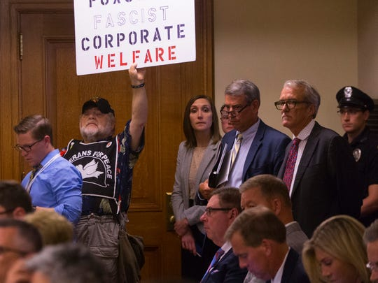 A lone protester is shown while Department of Administration Secretary Scott Neitzel speaks about incentives for Foxconn to locate in southeastern Wisconsin before the Assembly Committee on Jobs and Economy Thursday.