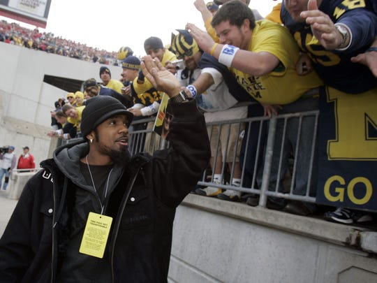 Former Michigan player Charles Woodson greets the fans as he walks down onto the field of Ohio Stadium on Saturday, Nov. 18, 2006 in Columbus, Ohio.