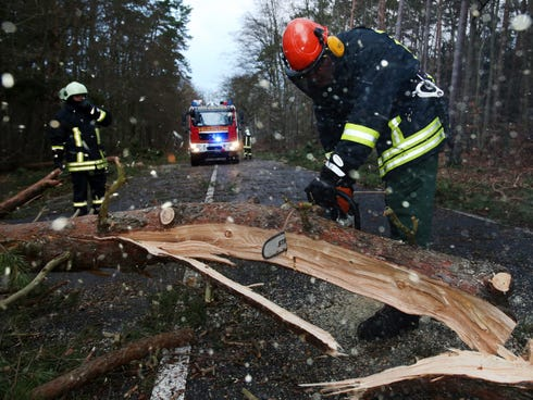 Firefighters cut a tree with a chain saw to clear the street after a Dec. 6 storm in Graal-Mueritz,��Germany.