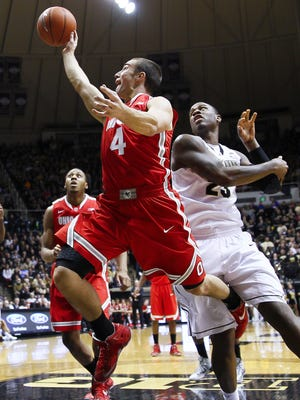 Aaron Craft of Ohio State shoots the ball as Jay Simpson of the Purdue Boilermakers defends from behind.