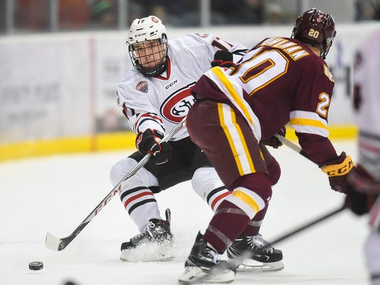 St. Cloud States's Jacob Benson passes the puck behind